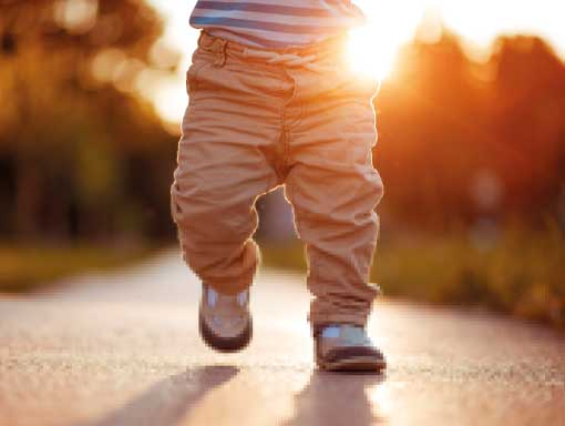 A baby walking on a sunny street