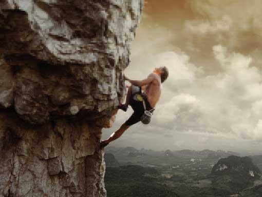 Guy climbing up a rock face